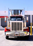 Refer Truck at dock. This is a picture of 18 wheeler refrigerated semi truck loading at a warehouse building dock Royalty Free Stock Image