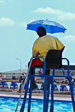 Referee. Official referee at a swimming competition, with umbrella, sitting on a tall chair Stock Photos
