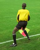 Referee. African referee with his red and yellow flag on green grass crossed by a white touchline Royalty Free Stock Image