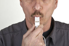 Referee blowing a whistle. Close up of a referee blowing a whistle stock photography