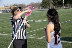 Referee checks a lacroose stick at a girls lacrosse game stock image
