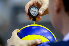 The referee counts the air pressure on the ball before the game Royalty Free Stock Photo