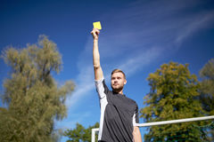 Referee on football field showing yellow card Stock Photos