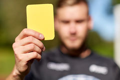 Referee on football field showing yellow card Stock Image