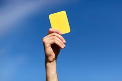 Referee on football field showing yellow card Stock Images