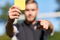Referee on football field showing yellow card Stock Photo