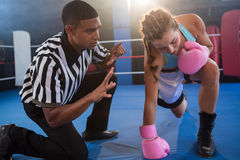 Referee gesturing to female boxer in ring Stock Photo