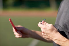Referee hands with red card on football field Royalty Free Stock Photo