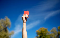 Referee hands with red card on football field Royalty Free Stock Photography
