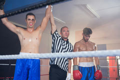 Referee holding hands of smiling male boxing winner by athlete Royalty Free Stock Photos