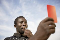 Referee Indicating Dismissal. Referee whistles while holding a red card to a player indicating a dismissal Stock Photos