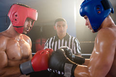 Referee looking at male boxers punching gloves Royalty Free Stock Photography