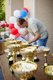 Referee prepares certificates and sports cups for awarding athletes. vertical stock photos