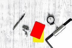 Referee preparing to competition. Yellow and red cards, stopwatch, whistle on wooden background top view.  royalty free stock image