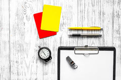 Referee preparing to competition. Yellow and red cards, stopwatch, whistle on wooden background top view copyspace Royalty Free Stock Photo
