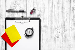 Referee preparing to competition. Yellow and red cards, stopwatch, whistle on wooden background top view copyspace. Referee preparing to competition. Yellow and stock images