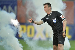 Referee remove flares from the football pitch Royalty Free Stock Photos