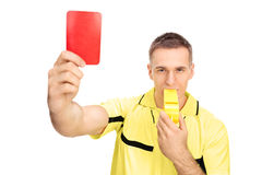 Referee showing red card and blowing huge whistle Stock Photos