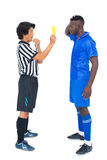 Referee showing yellow card to football player Royalty Free Stock Photo