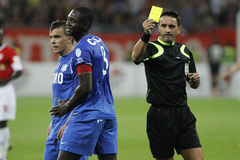 Referee shows the yellow card. Football referee, Sebastian Coltescu, shows the yellow card to Ousmane Viera in the match between Dinamo Bucharest and Pandurii Stock Photo