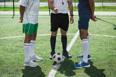 Referee and soccer players on soccer pitch starting game Stock Image