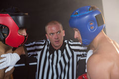 Referee stopping aggressive male boxers Stock Image