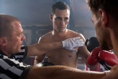 Referee stopping aggressive young male boxers Royalty Free Stock Images