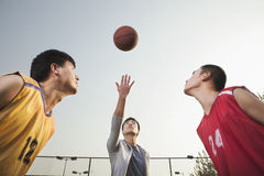 Referee throwing ball in the air, basketball players getting ready for a jump Royalty Free Stock Photos