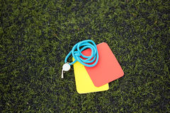 Referee whistle and caution cards on soccer field Stock Photos