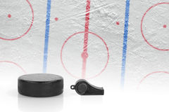 Referee whistle, the puck and hockey field Stock Photos