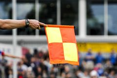Referees assistant and flag. A referees assistant waving their flag for an offside decision in football royalty free stock photography