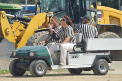 Referees Driving in Carryall Golf Cart. Referees for the Walworth County Fair Demolition Derby riding up in a Carryall brand Golf Cart.  In front of a CAT yellow Stock Photo