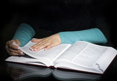 Reference book. Female hands on a particular page in a dictionary or other reference book. Dark background stock photo
