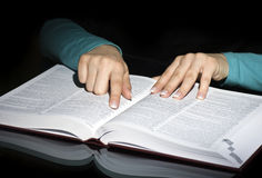 Reference book. Female hands with a finger pointing at a particular entry in a dictionary or other reference book. Dark background royalty free stock images