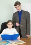 Referent und Schulmädchen mit Buch und Atlas Lizenzfreie Stockfotos