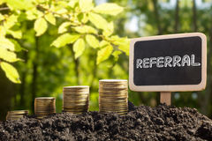 Referral - Financial opportunity concept. Golden coins in soil Chalkboard on blurred urban background