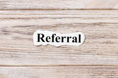 REFERRAL of the word on paper. concept. Words of REFERRAL on a wooden background royalty free stock image
