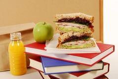 Refezione: panino di tacchino, mela, libri sullo scrittorio dell'aula fotografia stock libera da diritti