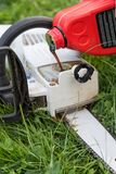 Refill oil in chainsaw. Refill oil in small cordless chainsaw for gardening - closeup royalty free stock images