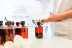 Refilling or cough syrup at a pharmacy Stock Photos