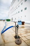 Refilling cruise ships water tanks. Ground service refilling docked cruise ships water tanks in port during a stop and sightseeing tour for passengers on cruise Royalty Free Stock Image