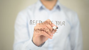 Refinance Your Mortgage, Man Writing on Transparent Screen Royalty Free Stock Photography