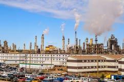 A refinaria de petróleo canadense a maior no fundo, estacionando no primeiro plano, tubulações de fumo imagem de stock