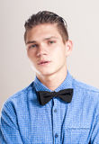 Refined man in a blue shirt with black bow tie. Royalty Free Stock Image