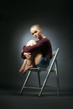 Refined model in stylish clothes sitting on chair Stock Photography