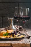 Refined still life of red wine, grapes and cheese. On metal tray on wooden table, dark background Royalty Free Stock Photos