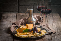 Refined still life of red wine, grapes and cheese. On metal tray on wooden table, dark background Stock Photography