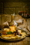 Refined still life of red wine, grapes and cheese. On metal tray on wooden table, dark background Royalty Free Stock Image