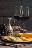 Refined still life of red wine, grapes and cheese. On metal tray on wooden table, dark background Stock Photo
