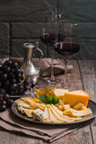 Refined still life of red wine, grapes and cheese. On metal tray on wooden table, dark background Royalty Free Stock Images